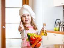 Kid weared as cook with vegetables at kitchen Royalty Free Stock Photography