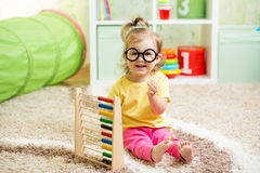 Kid weared eyeglasses playing with abacus Stock Image