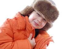 Kid wearing a coat and winter fur hat Stock Images