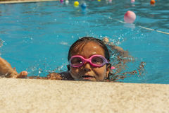 Kid wearing goggles breathing while swimming in the pool. Summer stock photography