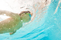 Kid wearing goggles swims under water of pool Stock Images