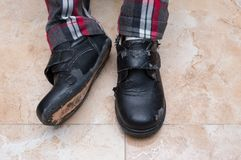 Kid wearing a pair of badly worn out leather shoe. S Royalty Free Stock Image