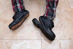 Kid wearing pair of badly worn out leather shoes. Kid wearing a pair of badly worn out leather shoes Stock Image