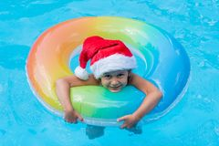 Kid wearing Santa Claus hat are swimming in a blue pool on a bright sunny day and smiling. Concept of happy new year and christmas stock photo