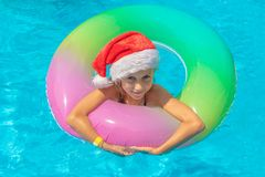 Happy girl floating in a blue pool in Santa hats on a blue background, look at the camera and smile. Concept of happy new year and stock photos
