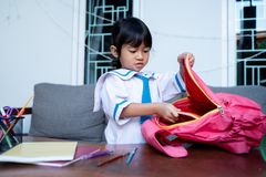 Kid Wearing School Uniform Put Some Book In To Her Backpack Stock Photography