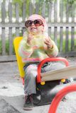 Kid wearing sunglasses on swing Royalty Free Stock Image