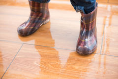 Kid wearing waterproof gumboots standing on wet floor Royalty Free Stock Photos