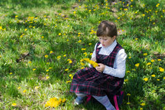 Kid weaves a wreath of dandelions Royalty Free Stock Photo