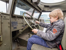 Kid at the wheel of a military vehicle Royalty Free Stock Images