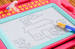 Kid white board with drawing. A kid magnetic drawing board with drawing of house, flowers stock photo