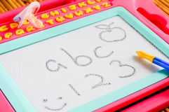 Kid white drawing board with abc and 123. A kid magnetic drawing board with abc and 123 written, pacifier royalty free stock images