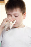 Kid in white drinks water Stock Photos