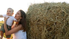 Kid in the white shirt sitting c young mother in a white dress near a haystack stock video footage