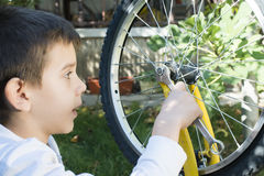 Kid who fix bikes Stock Photos