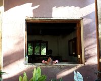 Kid in a window in a house in rural Carribbean close to Habana port. Kid in a window in a house in rural Carribbean close to port in summer during the season in Royalty Free Stock Image