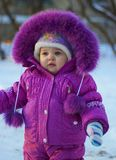 Kid in winter. Portrait of cute baby in overalls in winter Stock Photography