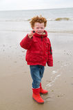 Kid at winter beach. Happy boy (4) in winter clothing at the beach, proudly showing the shell he has found. Photo taken on an early spring day royalty free stock photos