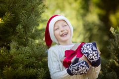 Kid at winter. Beautiful smiling boy in santa`s hat and mittens holding christmas gift standing by the tree, winter holiday concept Stock Image