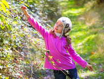 Kid winter girl picking mulberry berries in the forest. With wool cap Royalty Free Stock Images