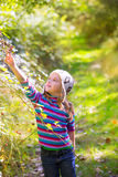 Kid winter girl picking mulberry berries in the forest. With wool cap Stock Photo