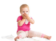 Kid wiping or cleaning nose with tissue on white