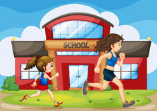 A kid and a woman running in front of the school Royalty Free Stock Image