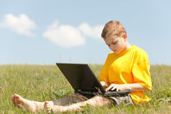 Kid is working on the laptop sitting on the meadow Royalty Free Stock Image
