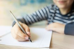 Kid writing in notebook. stock photography