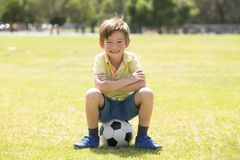 Kid 7 or 8 years old enjoying happy playing football soccer at grass city park field posing smiling proud sitting on the ball in Royalty Free Stock Photo