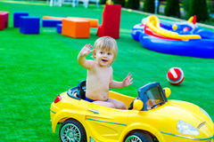 Kid in the yellow car on the playground Royalty Free Stock Photography