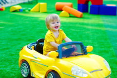 Kid in the yellow car on the playground. Cute and positive toddler driving yellow toy car and having fun on the playground Royalty Free Stock Images