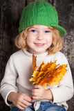 Kid with yellow maple leaves. Funny smiling kid holding yellow maple leaves. Autumn concept Stock Images