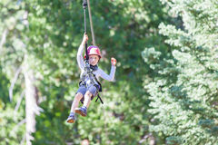 Kid ziplining. Positive little boy ziplining at outdoor treetop adventure park being active and brave Royalty Free Stock Photo