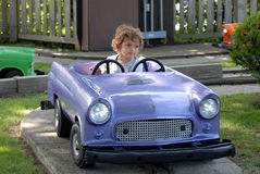 Kiddie Car Rider. A toddler riding a kiddie car on a track at an amusement park Royalty Free Stock Photo