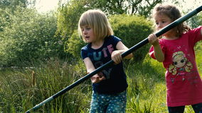 Kiddie Fishing Clip #6. Two little girls are catching together a big fish with a big fishing rod - part 1 stock video footage