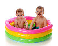 Kiddie Fun. A baby girl and her toddler brother playing in a kiddie pool.  Isolated on white Stock Photo