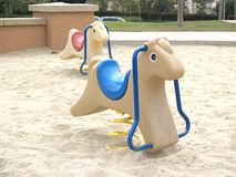 Kiddie Horse. Beige kiddy horse with blue seat in a sand playground Stock Image