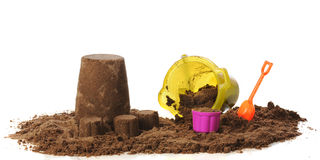 Kiddie Sand Creations. Early childhood efforts at creating a sand castle using a pail and colorful kitchen ontainer to pack wet sand. Isolated on white royalty free stock photography