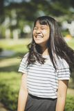 Kidding face of asian teenager showns forelock hair flowing by w. Ind stock photo