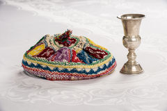 Kiddush Cup and Colorful Yalmulke on Linen Tablecloth. Kiddush cup and Israeli yamulke on linen tablecloth Royalty Free Stock Images