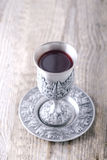 Kiddush cup with wine. Silver kiddush cup with wine on the wooden table Stock Photo
