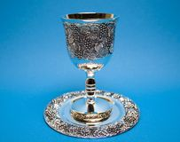 Kiddush Whine Cup and Saucer. Silver kiddush wine cup and saucer on the blue background Royalty Free Stock Photography