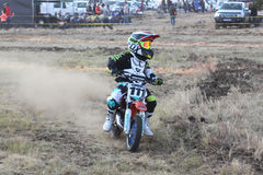 Kiddy motorbike rider speeding down track on mini motorbike. Stock Images