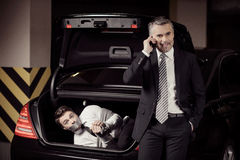 Kidnapped man. Tied up businessman lying in the car trunk and looking at camera while kidnapper talking at mobile phone Royalty Free Stock Images
