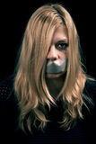 Kidnapped woman hostage with tape over her mouth. Portrait of scared kidnapped woman hostage with tape over her mouth Royalty Free Stock Photo