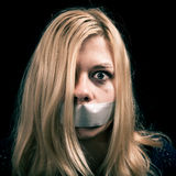 Kidnapped woman hostage with tape over her mouth Royalty Free Stock Photos