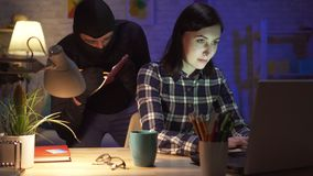 Kidnapper records important data from the girl`s laptop in a modern apartment. Young woman in a modern apartment works on a laptop, a masked thief behind her stock video