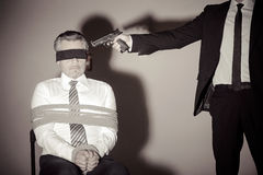Kidnapper and victim. Tied up businessman sitting at the chair while young man in formalwear aiming him with gun Stock Image