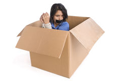 Kidnapping - helpless. A young woman tied up inside the box is thinking how to escape Royalty Free Stock Photo